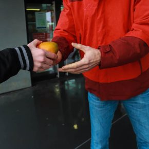 Übergabe einer Mango in fröhlichem Farbenspiel